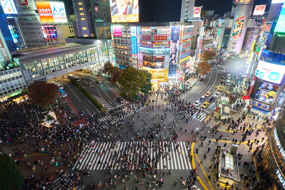 Crowds move through Tokyo's iconic Shibuya Crossing at night. Photo by  Timo Volz  on  Unsplash
